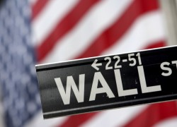 FILE - In this Sept. 25, 2008 file photo, a Wall St. street sign is shown in front of the American flag hanging on the New York Stock Exchange in New York. Stocks fell sharply Tuesday, Sept. 1, 2009, giving up earlier gains after the Institute for Supply Management said its index of manufacturing activity rose to 52.9 in August, up from 48.9 in July and well above the reading of 50.5 analysts had been expecting. (AP Photo/Mary Altaffer, file)