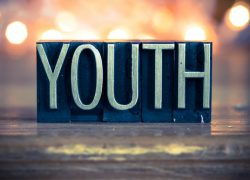The word YOUTH written in vintage metal letterpress type on a soft backlit background.